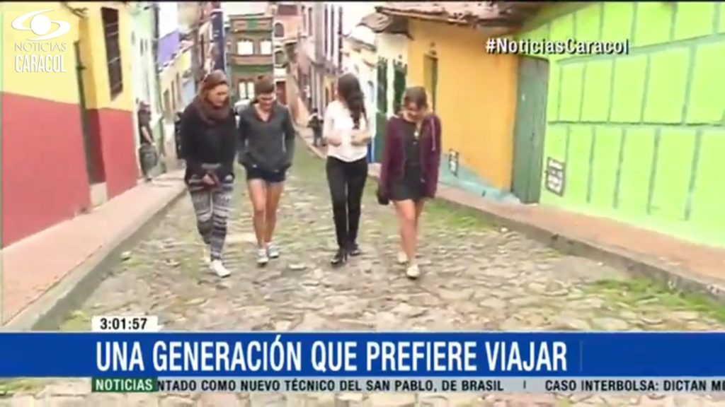Reporter Estefanía Zárate Angarita walking down the streets of the historic city centre of Bogotá along with three backpackers.